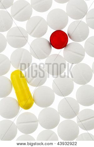 white and colored tablets, symbolic photo for medicine, remedies and pills addiction