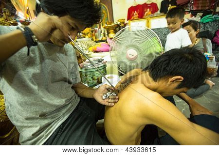 NAKHON CHAI, THAILAND - MAR 1: Unidentified master makes traditional Yantra tattooing on Mar 1, 2012 in Nakhon Chai, Thailand. Yantra tattoo also called Sak Yant practiced in Southeast Asian countries