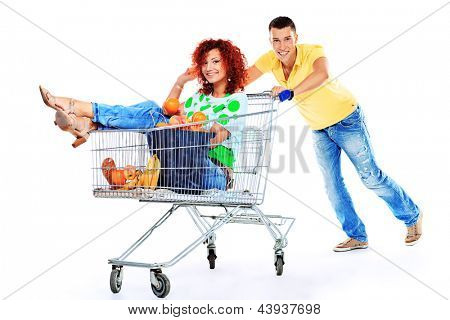 Cheerful couple with a shopping trolley. Isolated over white background.
