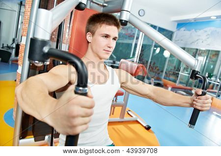 smiling fitness man at chest pectoral muscles exercises with training weight machine station in gym