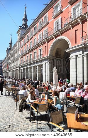 MADRID - MARCH 9: People sit at tables in cafe at Plaza Mayor on March 9 2012 in Madrid, Spain. In 2012 number of tourists in resorts of Spain increased 1.5 times compared to 2011.