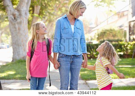 Madre e hijas caminando a la escuela en la calle suburbana