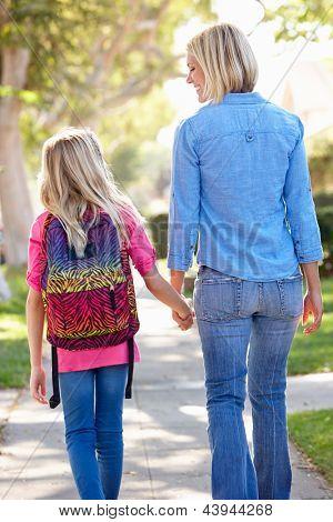 Madre e hija caminando a la escuela en la calle suburbana