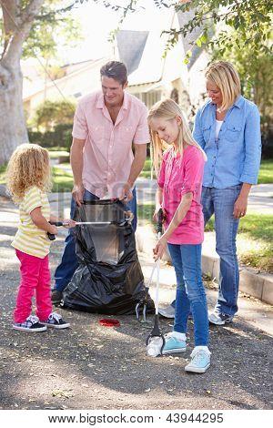 Family Picking Up Litter In Suburban Street