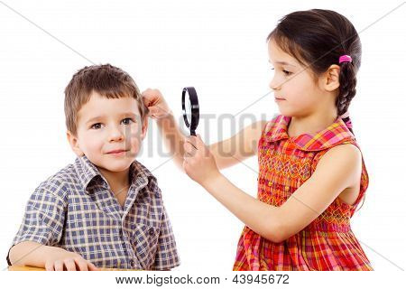 Girl looks to boy's ears through magnifier