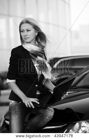 Young businesswoman with laptop sitting on the car