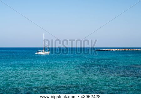 Seashore Of Cyprus Island With Rocky Coast And White Yacht In Mediterranean Sea
