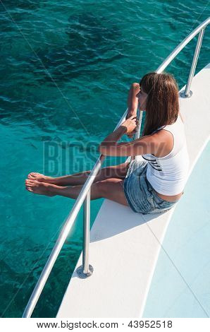 Pretty Young Woman Sitting On Shipboard With Legs Out