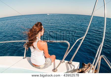Wide Angle View Of Pretty Young Woman Sitting On Shipboard With Legs Out