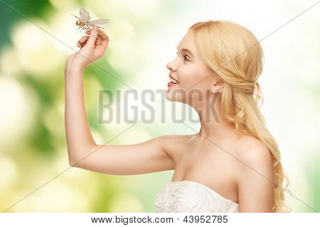 picture of beautiful woman with dragonfly in hand