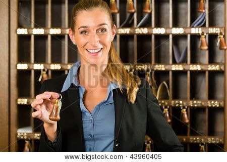 Reception of hotel - desk clerk, woman holding a key in the hand and smiling