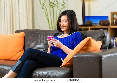 Young Indonesian woman sitting on the couch with text with a mobile phone or Smartphone