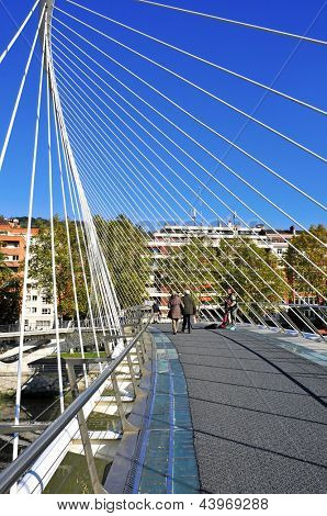 BILBAO, SPAIN - NOVEMBER 13: Zubizuri Bridge on November 13, 2012 in Bilbao, Spain. This tied arch footbridge over the Nervion River was designed by the famous architect Santiago Calatrava
