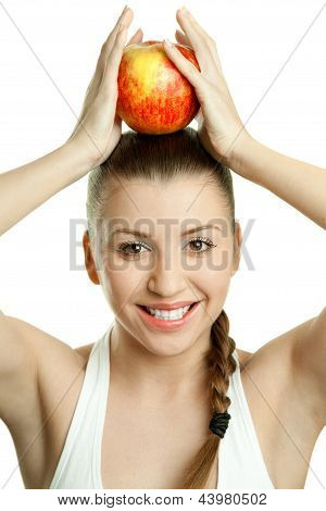 Beautiful young woman with red apple over her head
