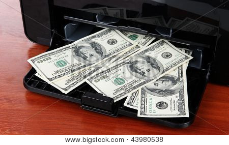 Printer printing fake dollar bills on wooden background