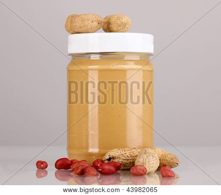 Delicious peanut butter in jar of peanut near on grey background