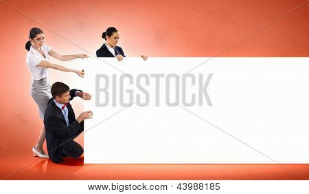Image of three young people holding blank banner against orange background. Place for text