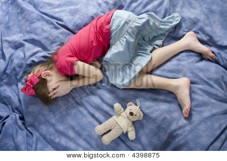 stören Sie wenig weinendes Mädchen auf dem Bett liegend