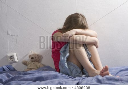 Little Sad Crying Girl Sitting On The Bed