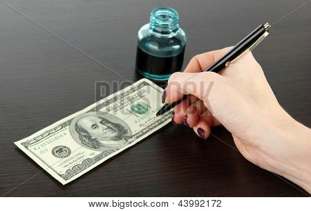 Making fake dollar on wooden background