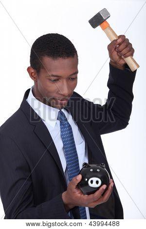 Man breaking a piggy bank open with a hammer