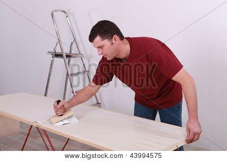 Man gluing wallpaper