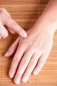 Picture of acupressure, acupuncture point hegu, li4. Photo shows how to find this point.