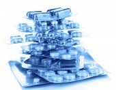 Capsules and pills packed in blisters in blue light isolated on white