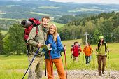 Smiling couple posing with hiking sticks and map on track