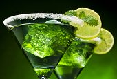 Closeup of green cocktails in martini glasses with ice cubes, lime slices, mint leaves and sugared e
