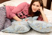 attractive cheerful teen girl in pajamas lying in her bedroom