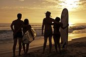 Summertme at the beach - friends with surfboards at sunset