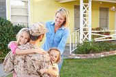 stock photo of soldiers  - Family Welcoming Husband Home On Army Leave - JPG