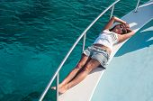 Happy Brunette Woman Laying On Shipboard Of Yacht. Copyspace