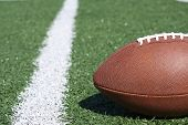 foto of ncaa  - An American football laying near the yardline - JPG