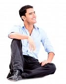 Relaxed business man sitting on the floor and smiling - isolated over white