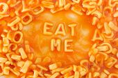 picture of eat me  - Pasta shaped letters spelling EAT ME within pasta shaped letters in tomato sauce - JPG