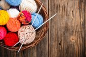 stock photo of wooden basket  - Balls of yarn in a basket with knitting needles - JPG