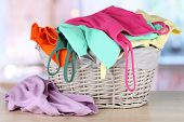pic of wooden basket  - Clothes in wooden basket on table in room - JPG