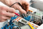 stock photo of fuse-box  - Hands of an electrician with multimeter probe at an electrical switchgear cabinet - JPG