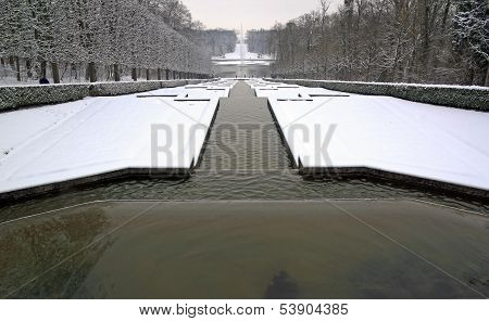 Perspective of ponds under the snow, a winter in a park in France