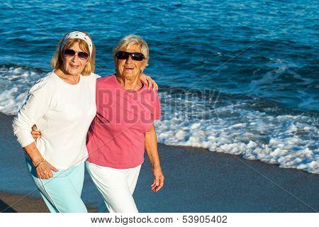 Senior Female Friends Walking Along The Beach.