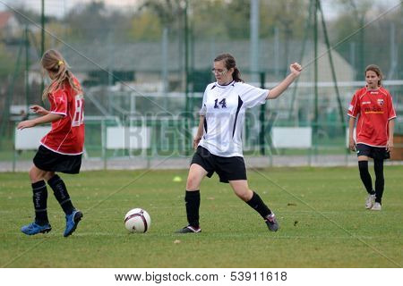 KAPOSVAR, HUNGARY - NOVEMBER 3: Klaudia Csiga (white 14) in action at Hungarian Championship under 15 women soccer game Rakoczi FC (white) vs Pecsi MFC (red) November 3, 2013 in Kaposvar, Hungary.