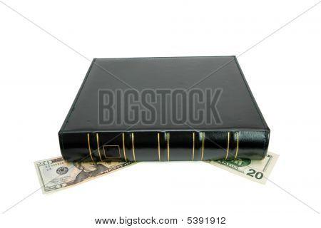 Black Book Presses Down Twenty Dollar Bills Isolated