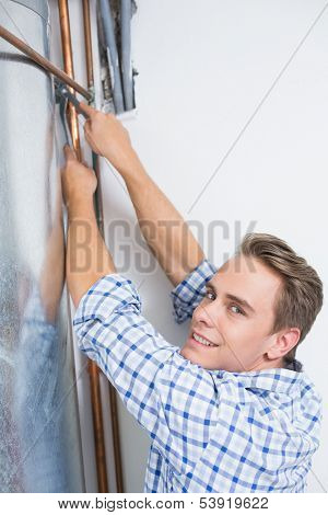 Side view portrait of a young technician servicing an hot water heater' pipes