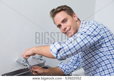 Portrait of a smiling plumber fixing water tap with pliers