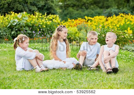Four children sit on grass at lawn, one boy sings with eyes closed, other listen and look at him