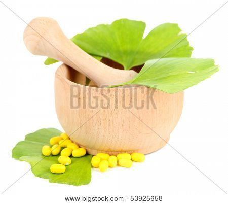 Ginkgo biloba leaves in mortar and pills isolated on white