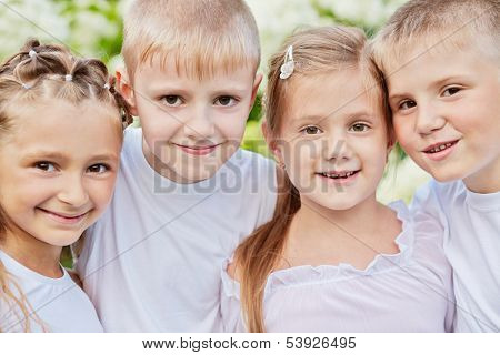 Closeup portrait of four smiling children standing head to head in summer park