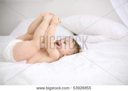 Happy little baby in nappy lies on white bed and holds feet at home. Shallow depth of field.